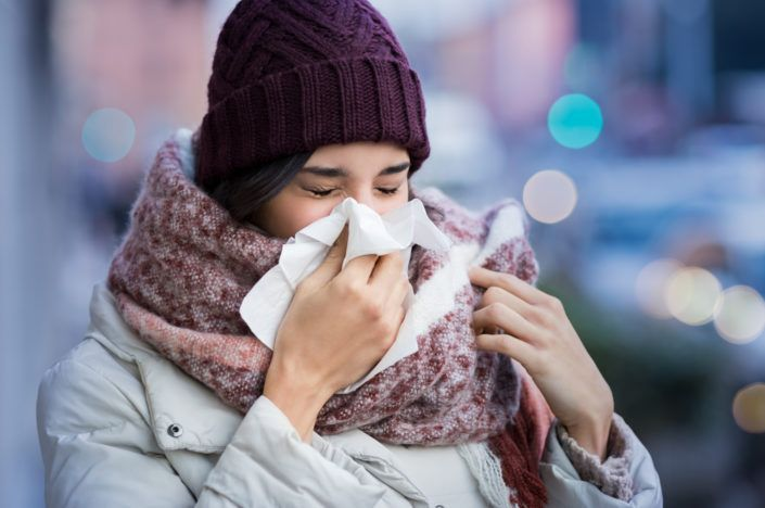 Woman blowing nose outdoor