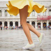 legs of a woman ina yellow skirt