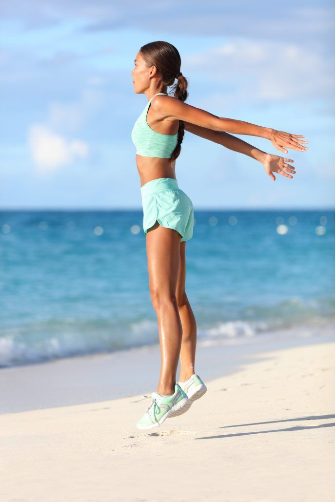 Fit woman training legs with hiit workout jumping squats exercises.
