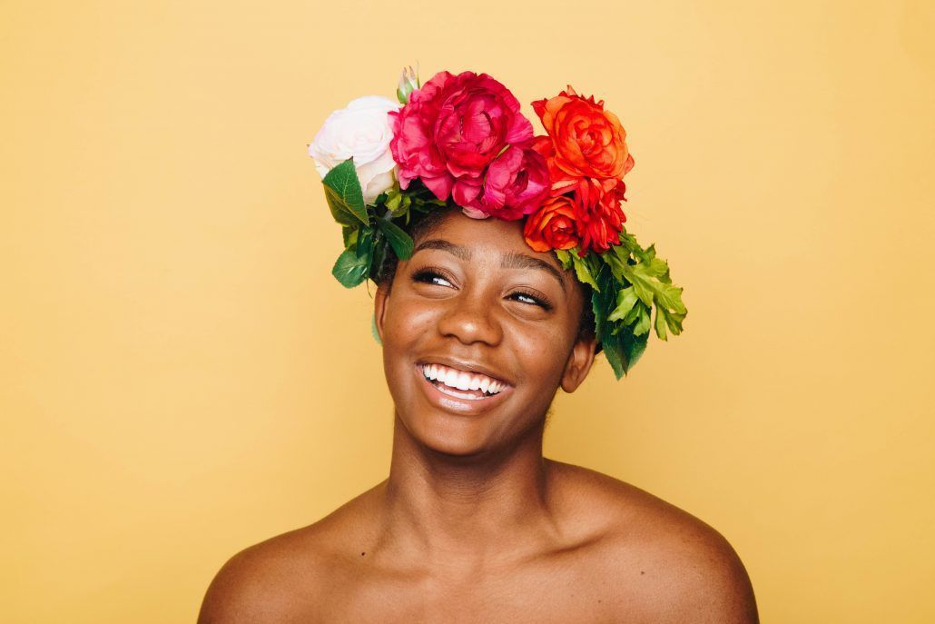 woman smiling with a flower crown in a yellow backround