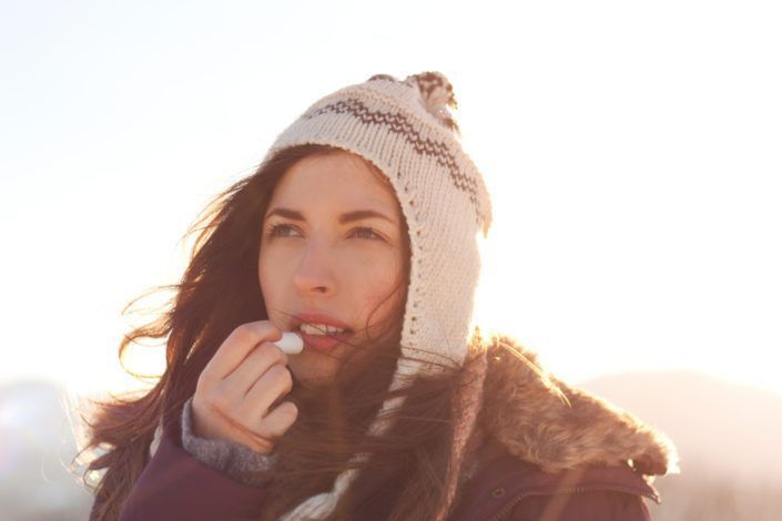 girl applying lip gloss in winter