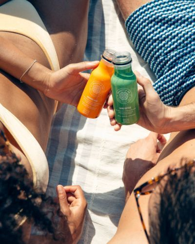 two people drinking juice on beach